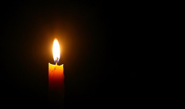 Licht für ein besseres leben - gelbe kerze brennt vor schwarzem hintergrund