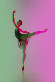 Licht. junger und anmutiger balletttänzer lokalisiert auf steigungsrosa-grüner wand in neon. kunst, bewegung, aktion, flexibilität, inspirationskonzept. flexible ballerina, schwerelose sprünge.