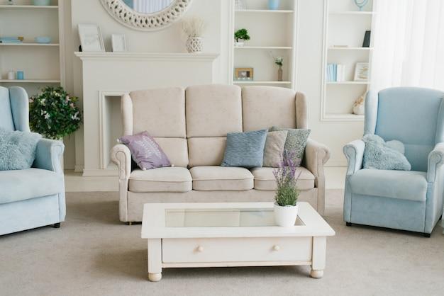 Licht mit blauem wohnzimmer: sofa, sessel, kamin und regale mit dekor, teil des spiegels
