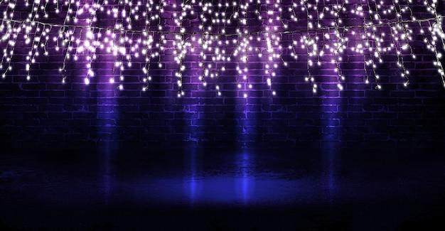 Lichtgirlande auf einer dunklen backsteinmauer reflexion von lichtern auf dem asphalt neonlicht-rauchsmog