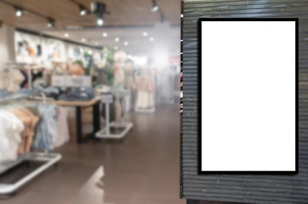 Lichtkasten oder leere schaukastenanschlagtafel mit unscharfem bild populärer frauenmode-kleidungsshopschaukasten im einkaufszentrum annoncieren
