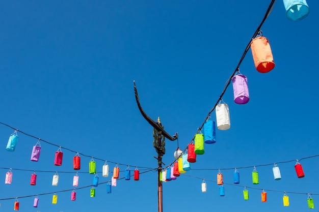 Lichtmasten und lampe mit buntem papier auf einem hellen blauen himmel.