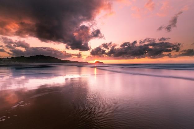Lichtreflexionen bei zarautz setzen mit der maus von getaria an der unterseite in einem sommersonnenuntergang auf den strand.