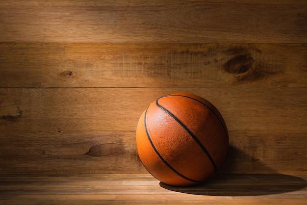 Lichtstrahl fallend auf alten basketball auf bretterboden