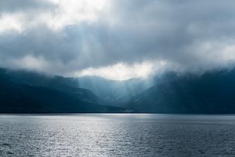 Lichtstrahlen scheinen durch dunkle Wolken. dramatischer Himmel mit Wolke