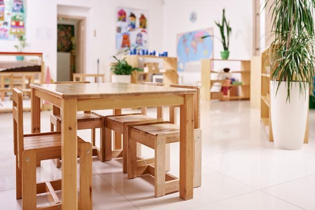 Lichtunterricht im montessori-kindergarten. hölzerner kindertisch mit stühlen im vordergrund.