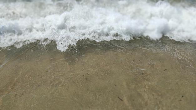 Lichtwelle auf sand des meeresstrandes, nah oben