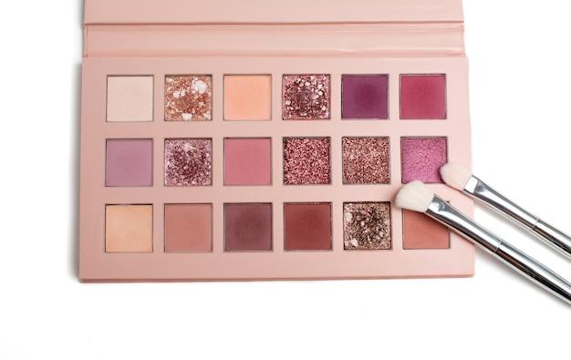 Lidschatten-palette in rosa farben mit zwei kosmetikpinsel auf weißem hintergrund