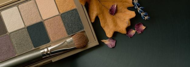 Lidschatten-palette schminken und mit trockenen blütenblättern in warmen farben bürsten.