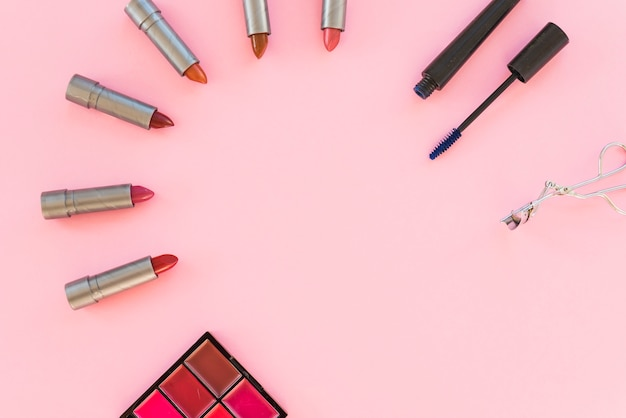 Lidschatten-palette; verschiedene lippenstift-töne; wimperntusche; über rosa hintergrund angeordnet