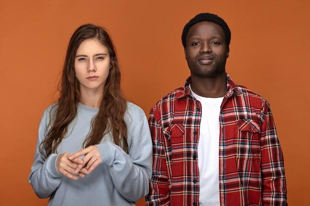 Liebe, beziehungen, menschen und lifestyle-konzept. modisches interraciales paar, das isoliert posiert, gereizte blicke verärgert, negative haltung ausdrückt, grimasse verzieht, frau misstrauisch