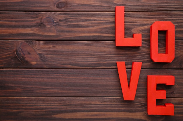 Liebe der roten buchstaben auf braunem hintergrund. liebe wort.