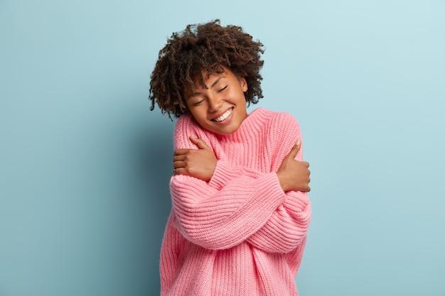 Liebe dich selbst konzept. foto der schönen lächelnden frau umarmt sich, hat hohes selbstwertgefühl, schließt die augen vor genuss
