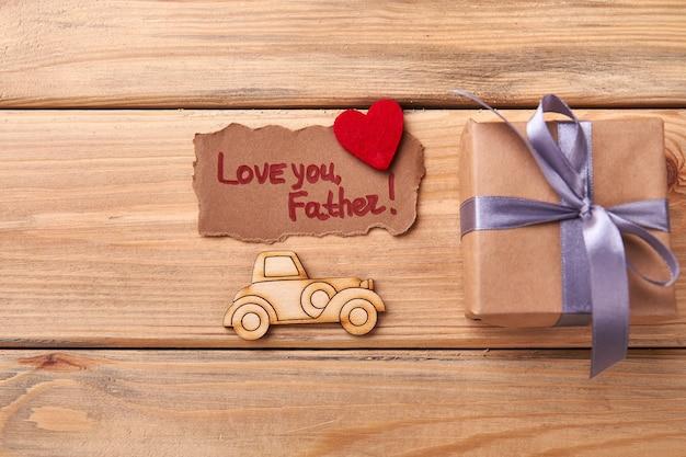 Liebe dich vaterkarte. brandmalerei-auto in der nähe von geschenkbox. drücken sie ihre liebe durch handarbeit aus.