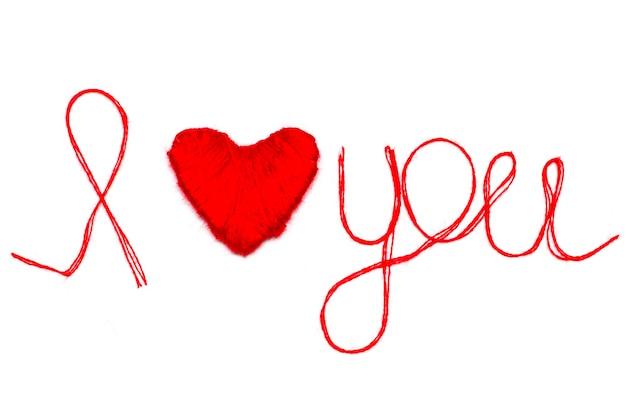 Liebe dich worte und herzsymbol aus rotem faden isoliert für deinen valentinstag