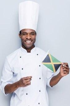 Liebe es, nationales essen zu kochen. selbstbewusster junger afrikanischer koch in weißer uniform mit flagge von jamaika holding