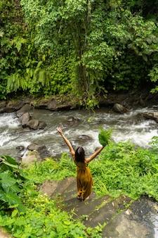 Liebe exotische natur. erfreutes mädchen, das beim gehen die arme hebt und die wilde balinesische aussicht genießt