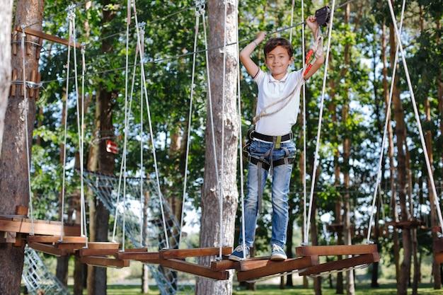 Liebe extrem. freudiger jugendlicher junge, der auf den schaukeln an einem seilpark steht und lächelt, während er für die kamera aufwirft