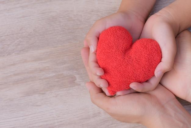 Liebe, familienkonzept. erwachsenen- und kinderhände, die handgemachtes rotes herz auf hölzernem backgroun halten