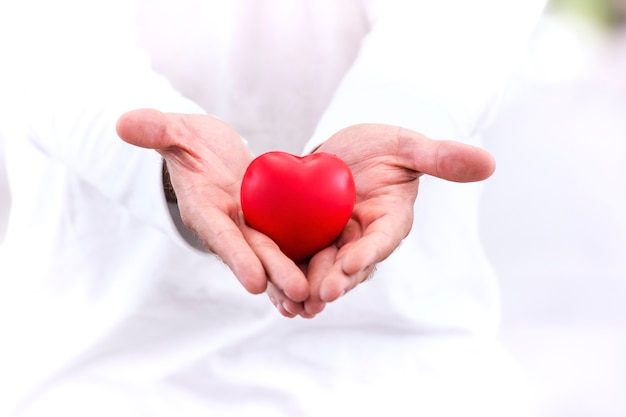 Liebe & gesundes konzept; rotes herz in der hand, pass auf mit liebe.