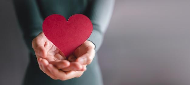 Liebe, gesundheitswesen, spende und wohltätigkeitskonzept. nahaufnahme von freiwilligen mit einem herzform-papier