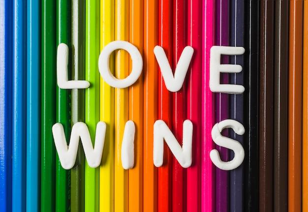 Liebe gewinnt wörter und lgbt-flagge von bleistiften