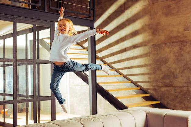 Liebe gymnastik. fröhliches kind, das ein lächeln auf dem gesicht behält, während es sich im sport anstrengt