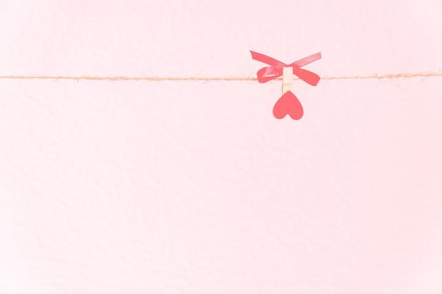 Liebe hintergrund. pin mit rotem herzen auf einer natürlichen schnur, die einen roten bogen hält.