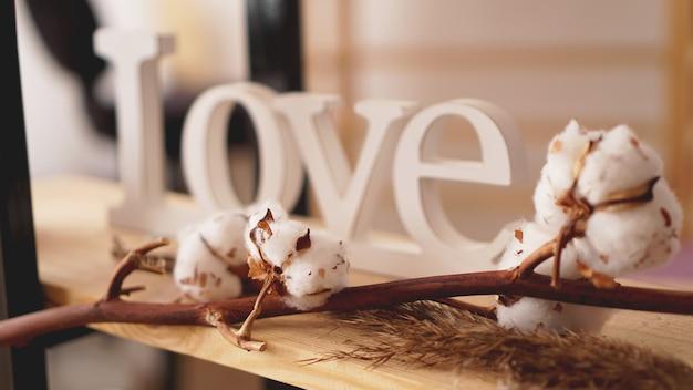 Liebe holzbuchstaben, vintage-stil und baumwollblume - unscharfer hintergrund für banner und einladungskarte