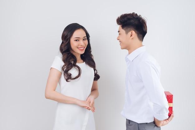 Liebe. hübscher junger vietnamesischer mann, der der schönen frau zu hause ein geschenk gibt