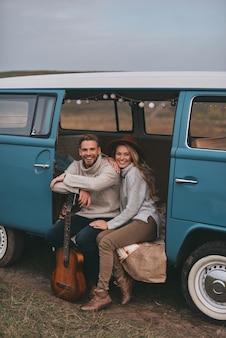 Liebe inspiriert sie. schönes junges paar lächelnd und kamera betrachtend, während im blauen retro-art-minivan sitzt
