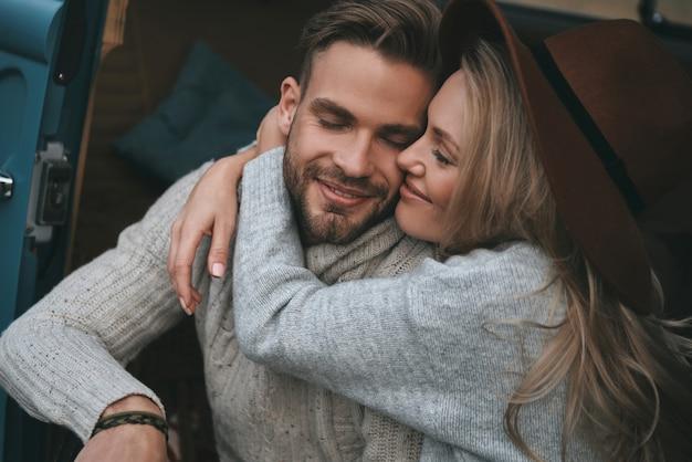 Liebe ist der größte schatz. schönes junges paar, das umarmt und lächelt, während im retro-art-minivan sitzt
