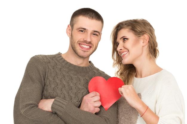 Liebe ist ein geschenk. porträt eines schönen glücklichen paares, das rotes papierherz hält, das freudig lokalisiert auf weiß lächelt