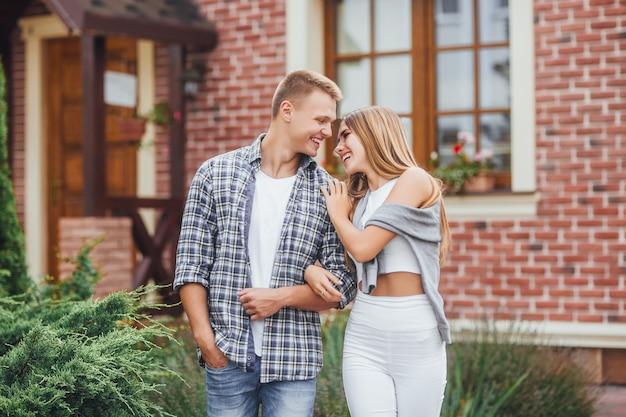 Liebe ist in der luft. glückliches junges paar, das draußen umarmt und lacht. schöne familie in der nähe des hauses.