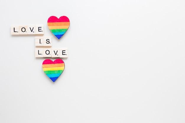 Liebe ist liebesaufschrift mit zwei regenbogenherzen