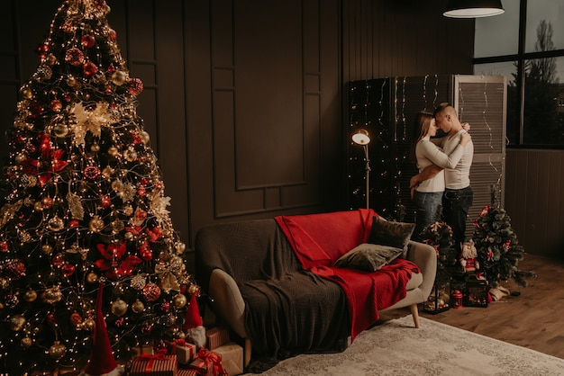 Liebe junge paar mann und frau umarmen küssen in der nähe eines weihnachtsbaumes.