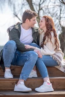Liebe. junger erwachsener mann und frau, die sich zärtlich und liebevoll ansehen, sitzen auf stufen in der natur