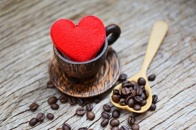 Liebe kaffee konzept. herz in hölzerner kaffeetasse mit kaffeebohnen romantischer liebes-valentinstag auf holz