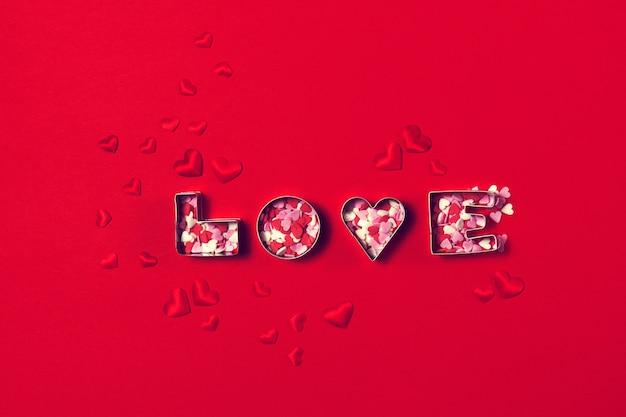 Liebe konzept mit buchstaben liebe und herzen auf rotem hintergrund. t