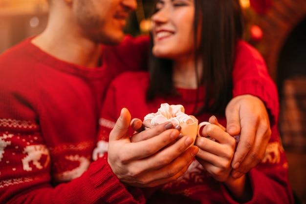 Liebe paar warme hände auf einer tasse kaffee, romantische weihnachtsfeier. weihnachtsferien, mann und frau glücklich zusammen, festliche dekoration
