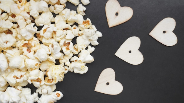 Liebe popcorn-konzept. horizontales foto. süßes essen. klassisches gesalzenes popcorn mit holzherzen auf einer schwarzen oberfläche
