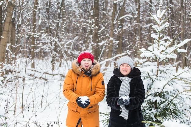 Liebe, saison, freundschaft und menschenkonzept - glücklicher junger mann und frau, die spaß haben und mit schnee im winterwald spielen.