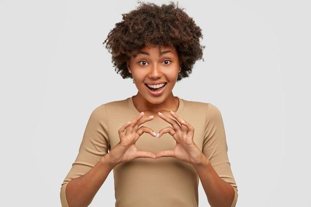 Liebe und frieden für dich. freundliche glückliche junge schöne afroamerikanische frau zeigt herzzeichen über brust