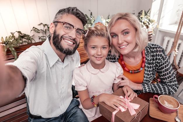 Liebe und glück. erfreutes lächeln der vereinigten familie, während sie zusammen für ein foto posiert