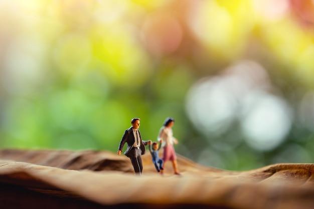 Liebe und glückliche familie. work-life-balance-konzept. miniatur des vater-, mutter- und sohnhändchenhaltens und gehens auf trockenes blatt im park