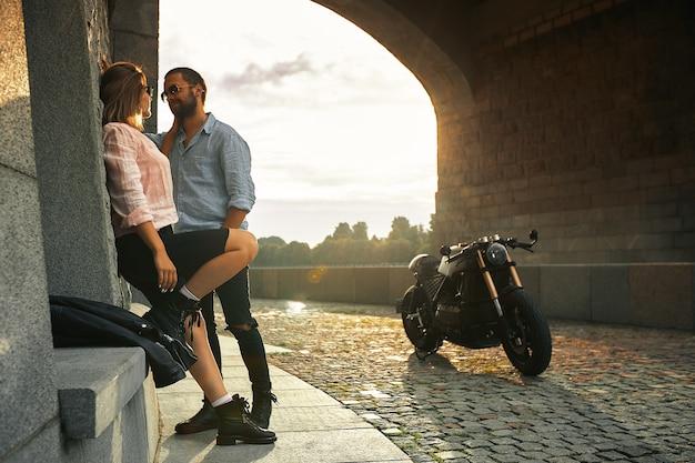 Liebe und romantisches konzept. paar verliebt in sonnenuntergang stehen an der wand kuss und umarmen unter der brücke neben motorrad. mann mit bart, der frauen umarmt, zärtlichkeit.