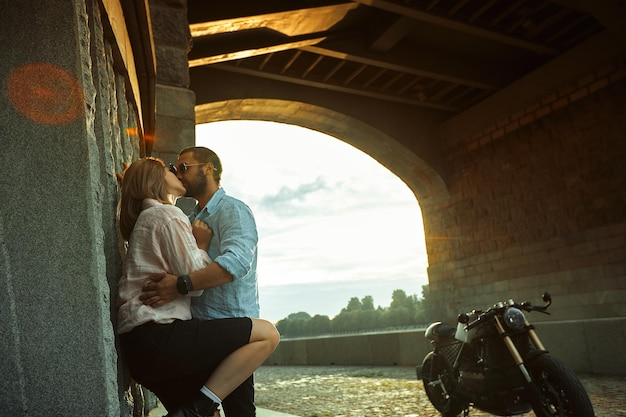 Liebe und romantisches konzept. paare, die in den sonnenuntergang verliebt sind, stehen an der wand, küssen und umarmen sich unter der brücke neben dem motorrad. mann mit bart umarmt womans, zärtlichkeit.