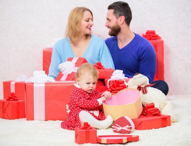 Liebe und vertrauen in die familie. bärtiger mann und frau mit kleinem mädchen. online einkaufen. vater, mutter und tochter kind. glückliche familie mit geschenkbox. valentinstag. rote kästen. alles was du brauchst ist liebe.