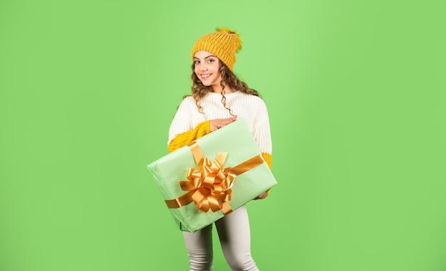 Liebe urlaub. winterferien. kleines mädchen make-up gesicht halten geschenkbox. kind halten geschenkbox. glücklicher kunde. internationaler kindertag. familien tradition. schönes geschenkpaket. hergeben.