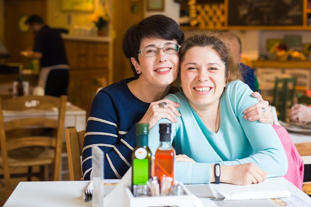 Liebe von mutter und tochter. glückliche frauen in einem netten café mit kopienraum auf unscharfem hintergrund. alte frau und ihre erwachsene tochter im café. muttertag.